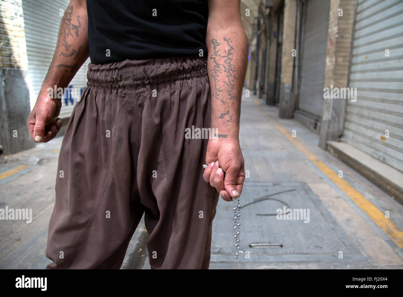 A man shows tattoos on his arms written in Persian in the grand bazaar of Tehran , Iran - Stock Image