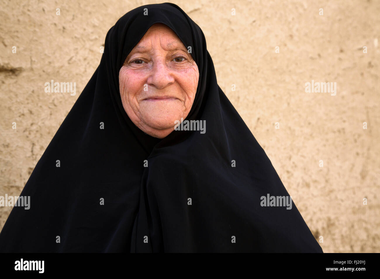 Portrait of old Iranian woman covered with traditonal black hijab islamic veil in Yazd, Iran - Stock Image