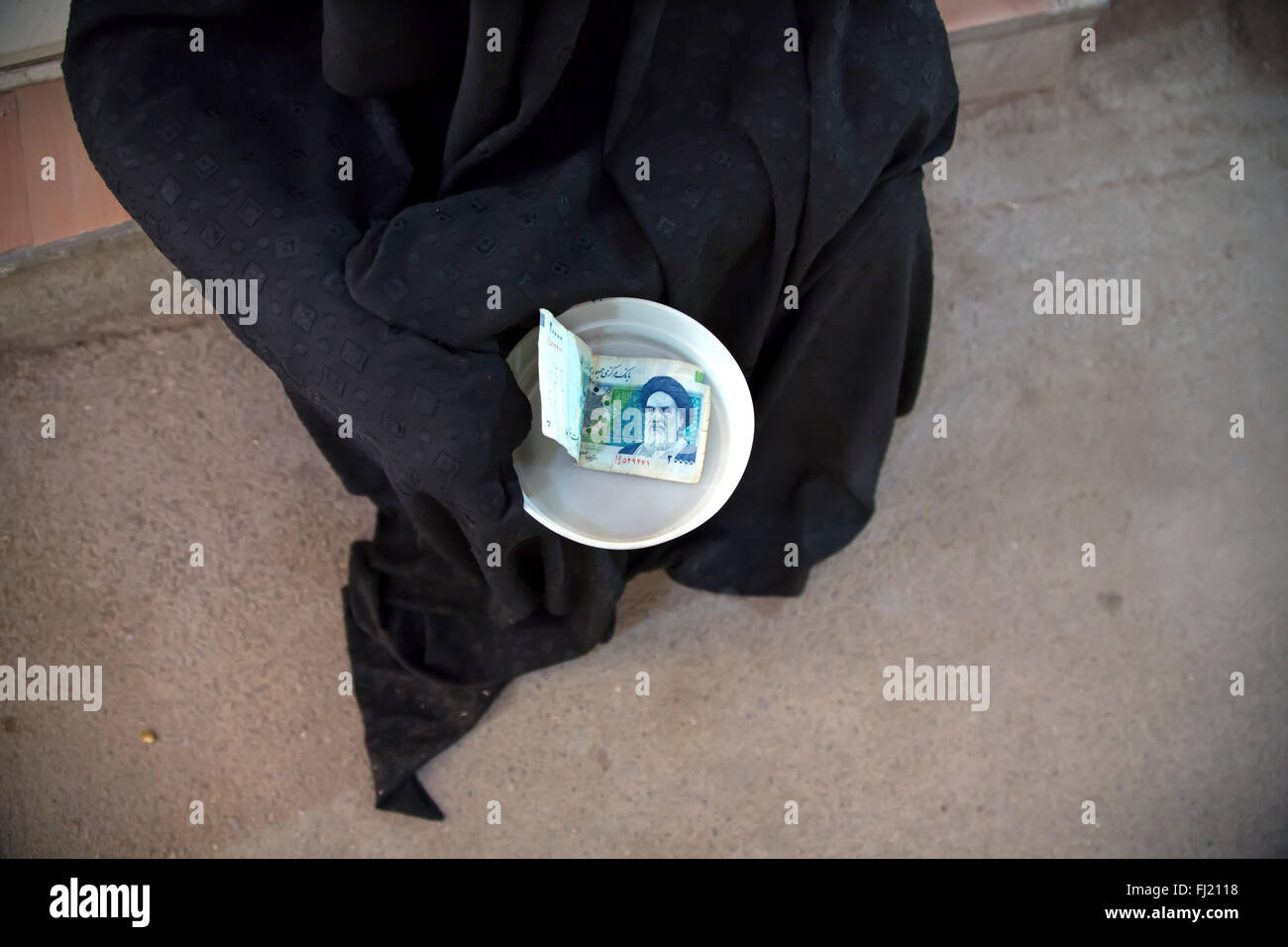 Beggar woman covered with hijab in the streets of Ispahan , Iran - Stock Image