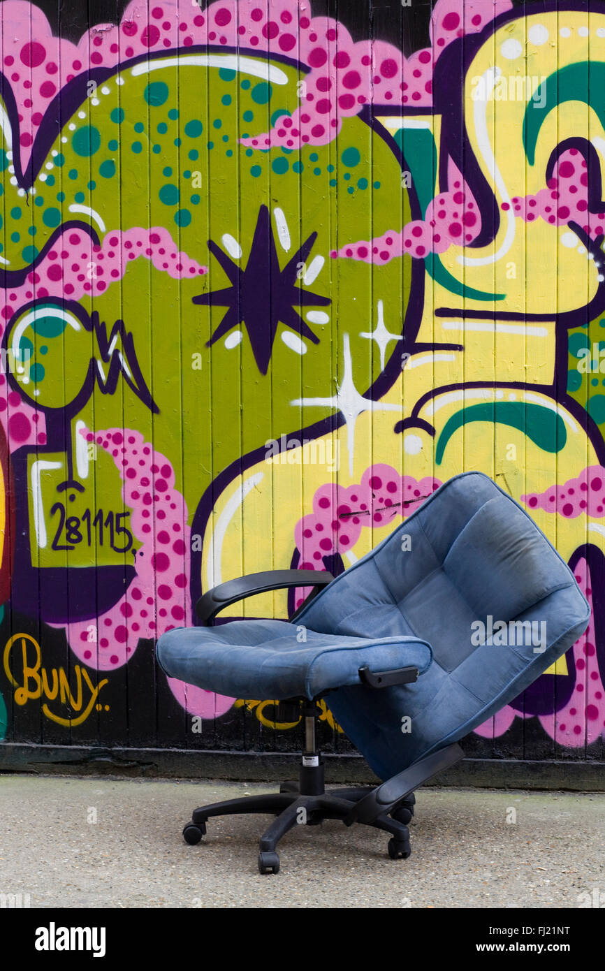 Broken Chair in front of a wall of Graffiti London - Stock Image
