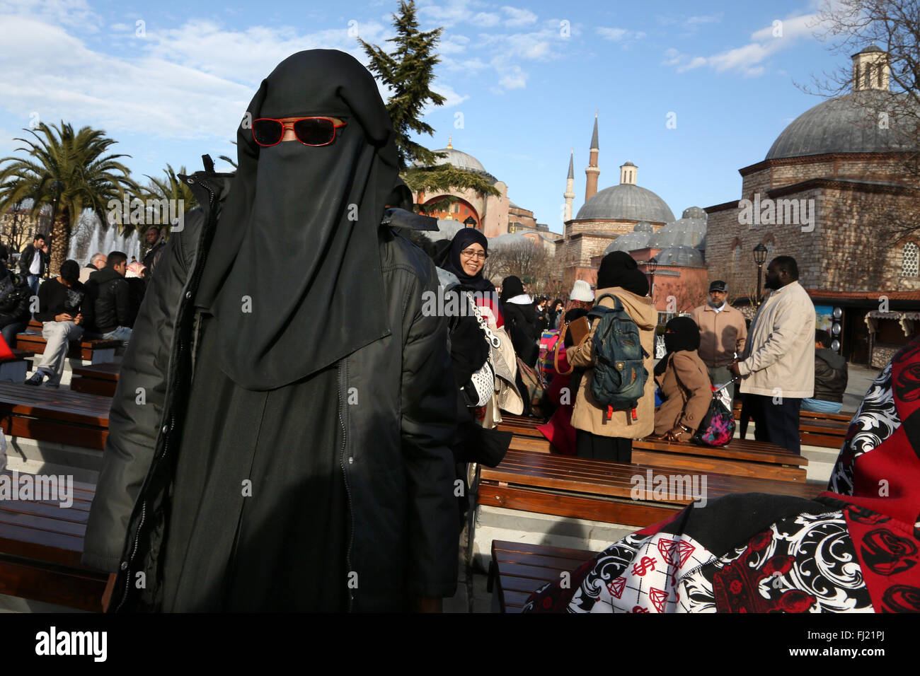 A woman wears niqab with red sunglasses in Istanbul - Stock Image