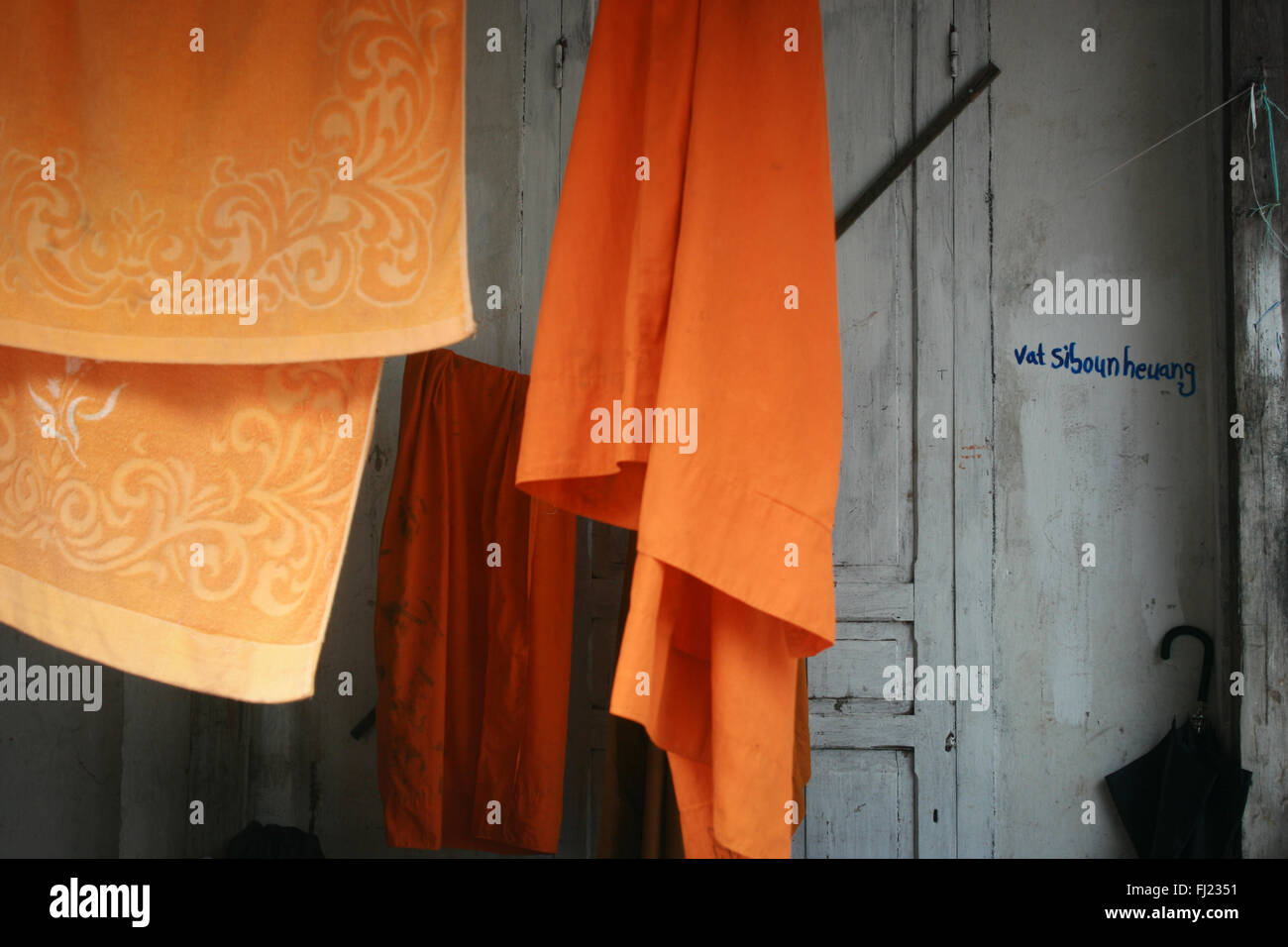 Orange safran colored traditional dress Buddhist monk in Luang Prabang , Laos, Asia - Stock Image