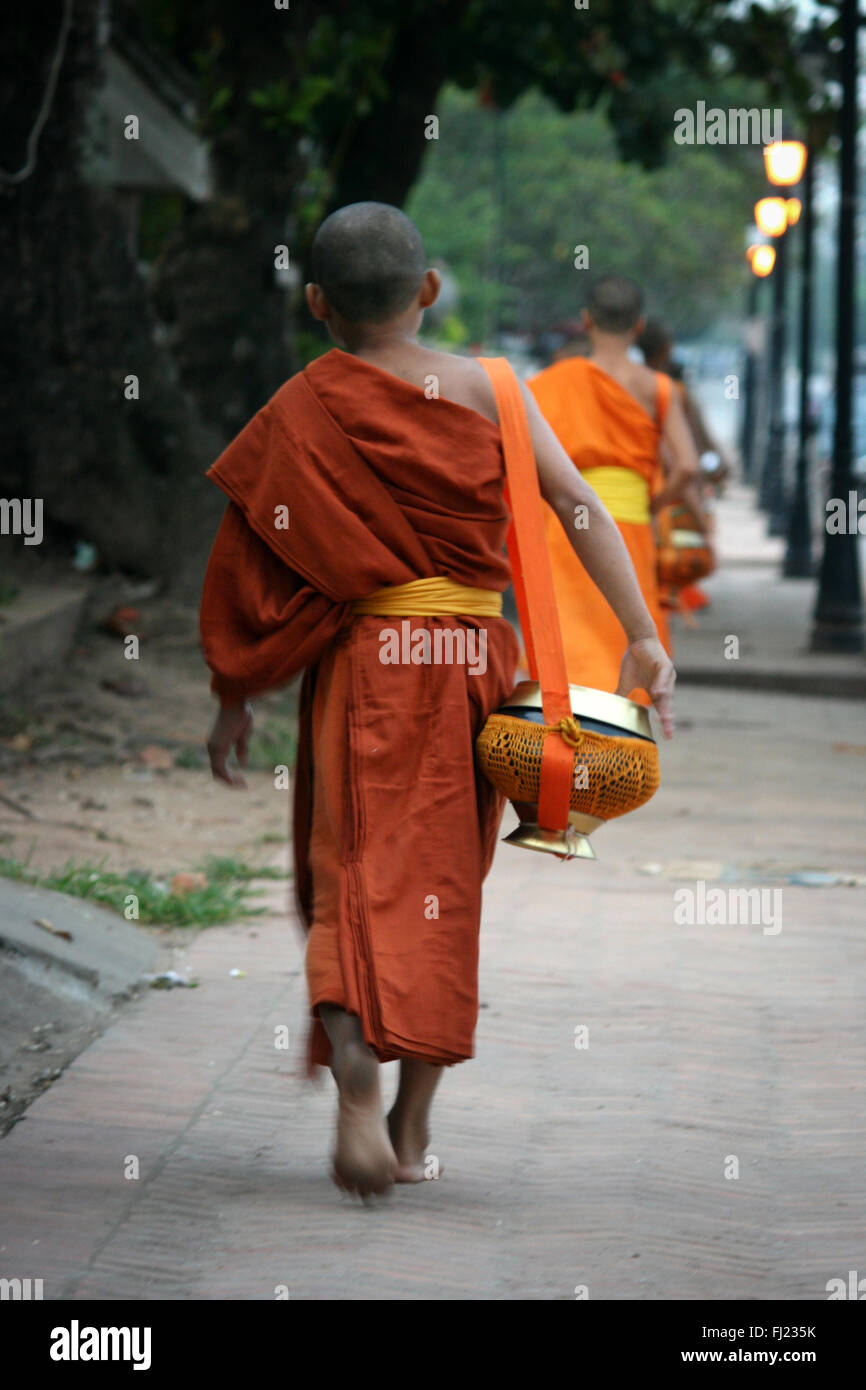 Buddhist monk walking in the streets of in Luang Prabang , Laos, Asia - Stock Image