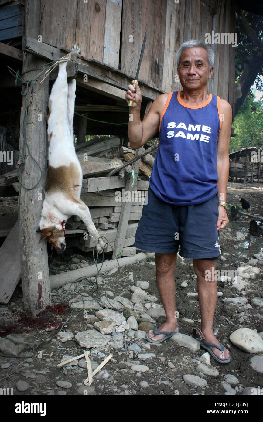 Man killing dog for eating in Vang Vieng, Laos, wearing 'same same' T shirt - Stock Image