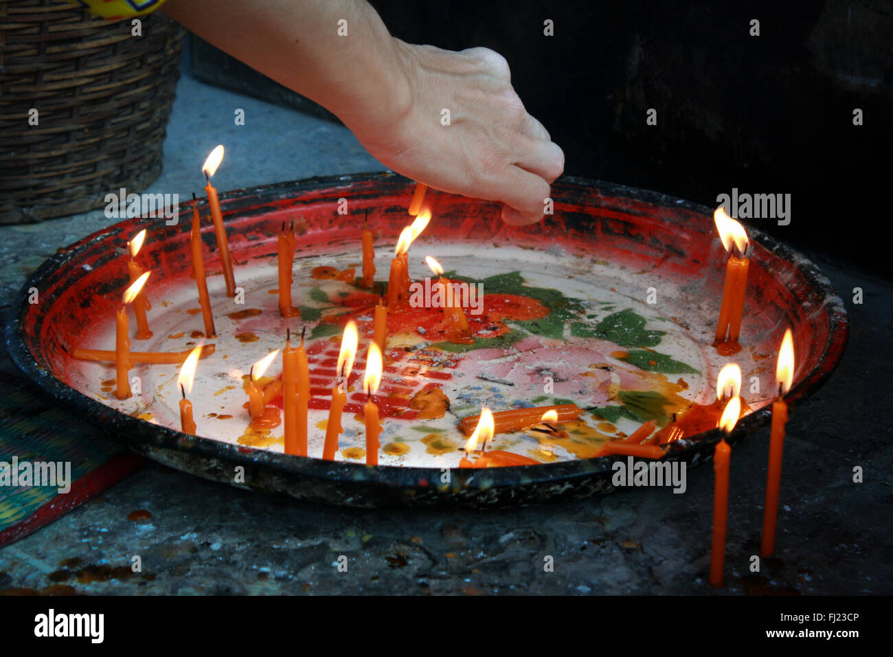 Woman lighting candles in a temple in Vientiane, Laos - Stock Image