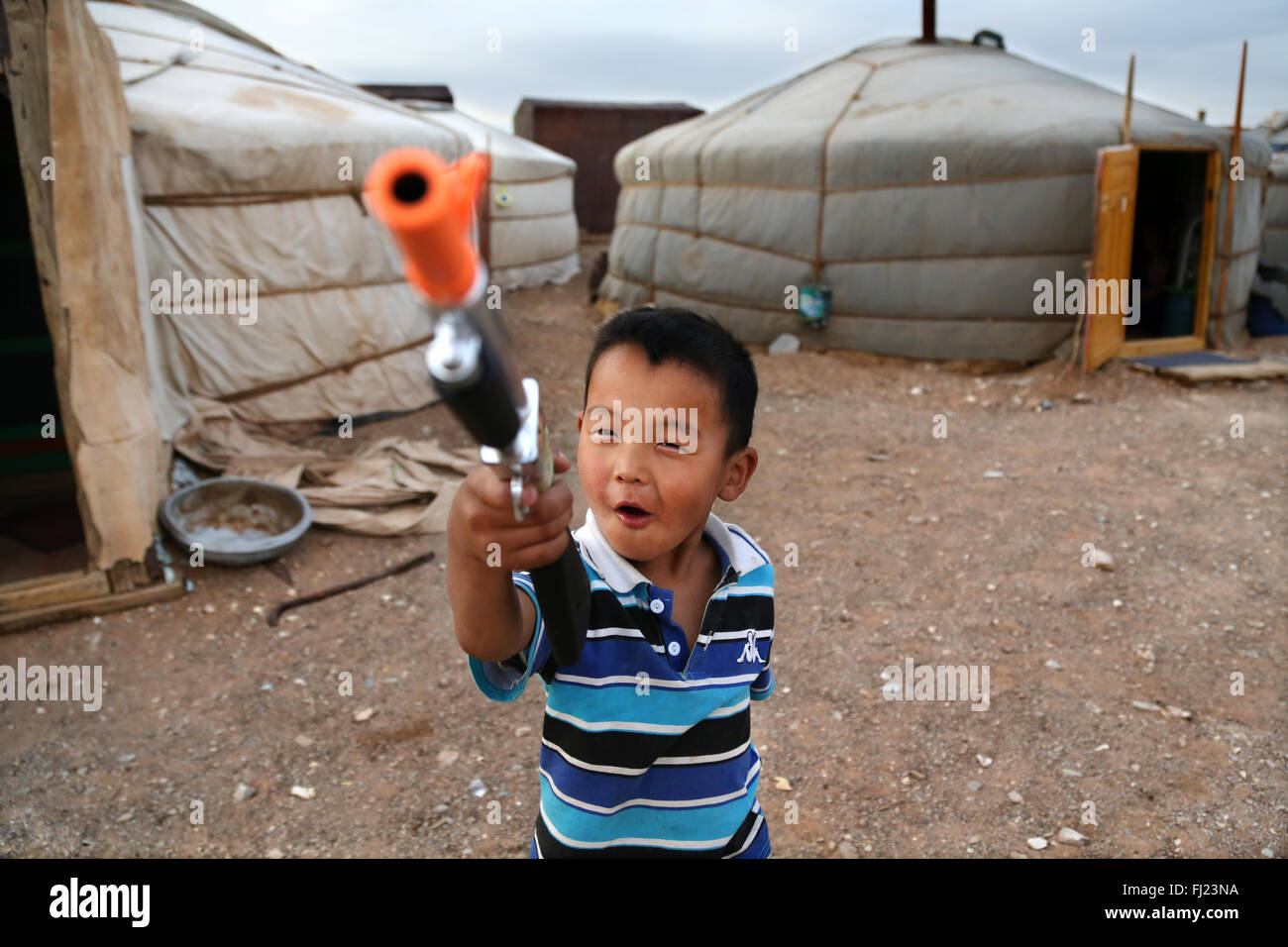 Portrait of a child kid playing with plastic gun in yurt ger camp  in Mongolia - Stock Image