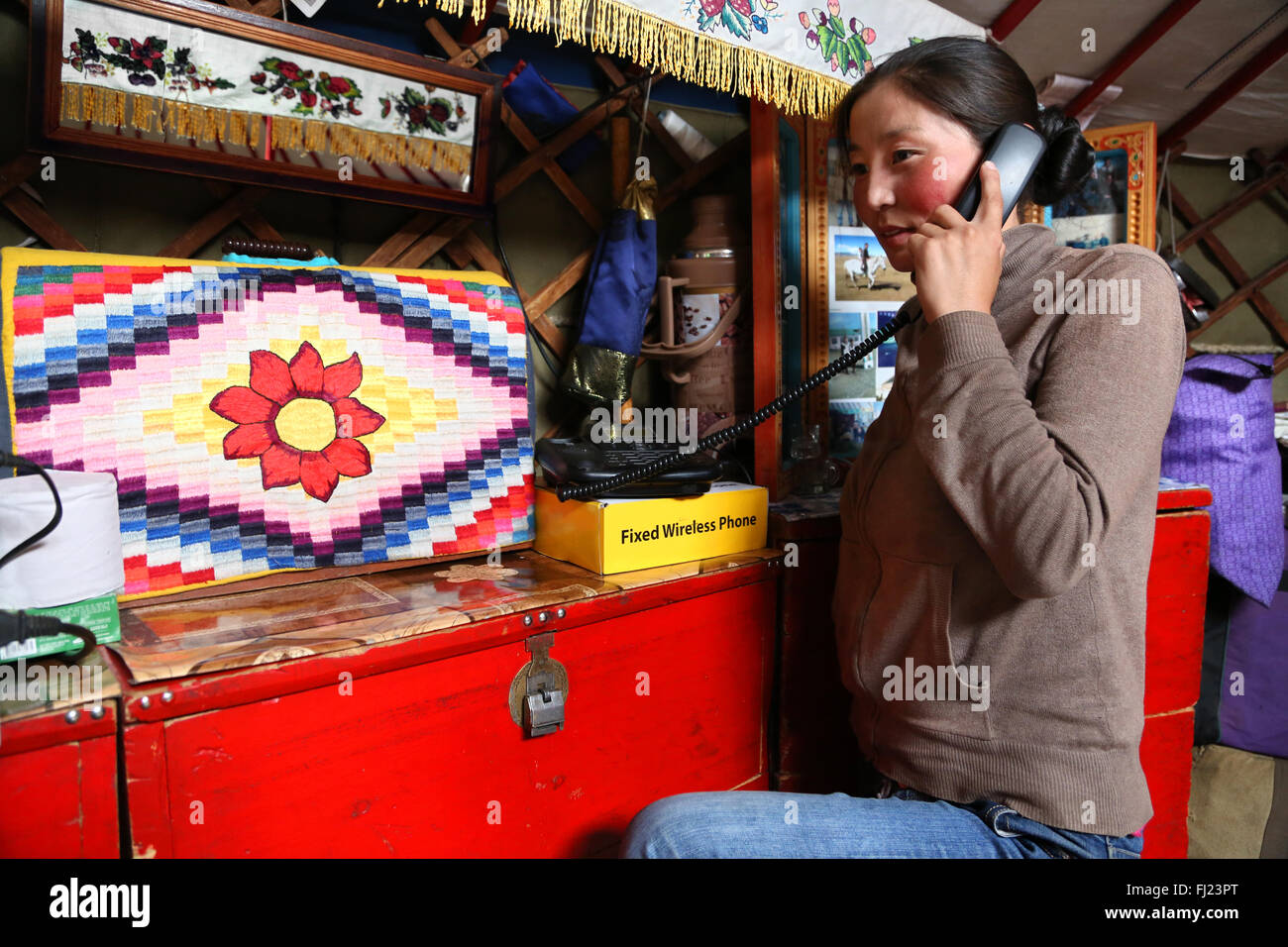 Woman making phone call in her yurt in the steppes in the middle of nowhere in Mongolia - Stock Image