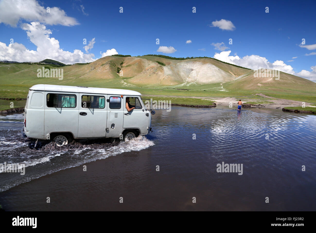 Old Russian van travelling in Mongolia through a river in the middle of nowhere - Stock Image