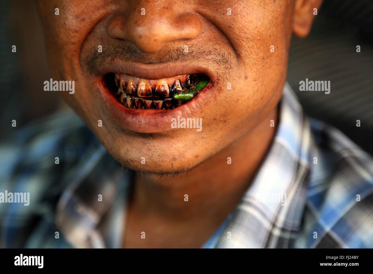Man chewing pan massala betel in the streets of Rangoon Myanmar - Stock Image