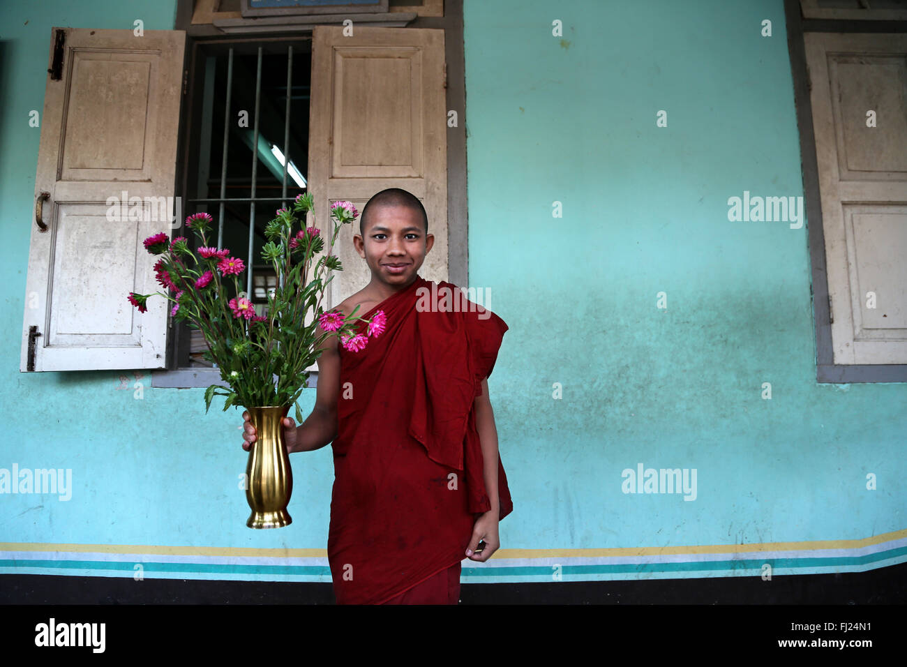 Young buddhist monk with flowers in monastery in Amarapura, Myanmar - Stock Image