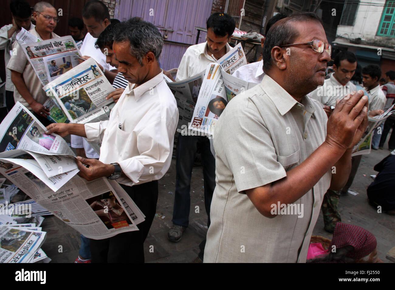People reading newspapers in the streets of Katmandu, Nepal - Stock Image