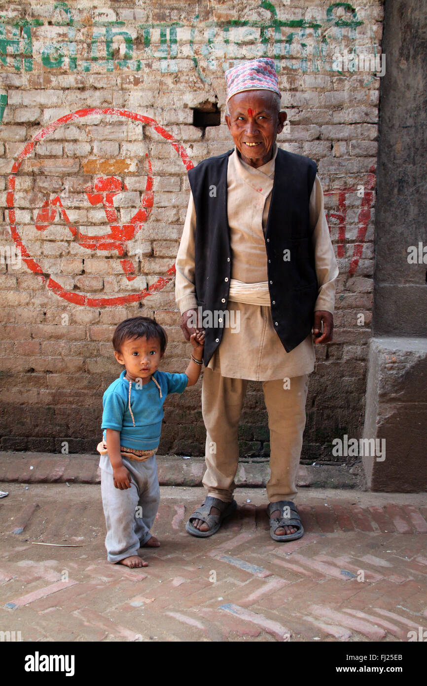 Portrait of Nepalese Newar  grandfather with grandson with  Communist symbol , Hammer and sickle - Stock Image