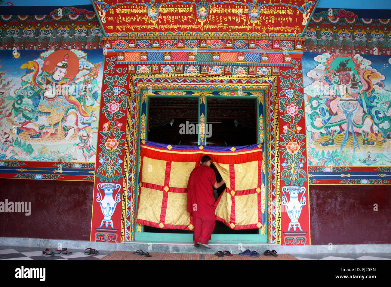 Buddhist monk entering gompa in Boudhanath, Nepal Stock Photo
