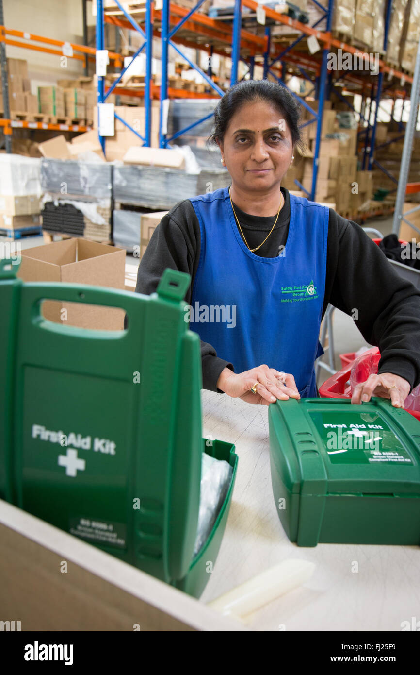 Woman packing First Aid Kit Boxes in a Warehouse in Hendon, England - Stock Image