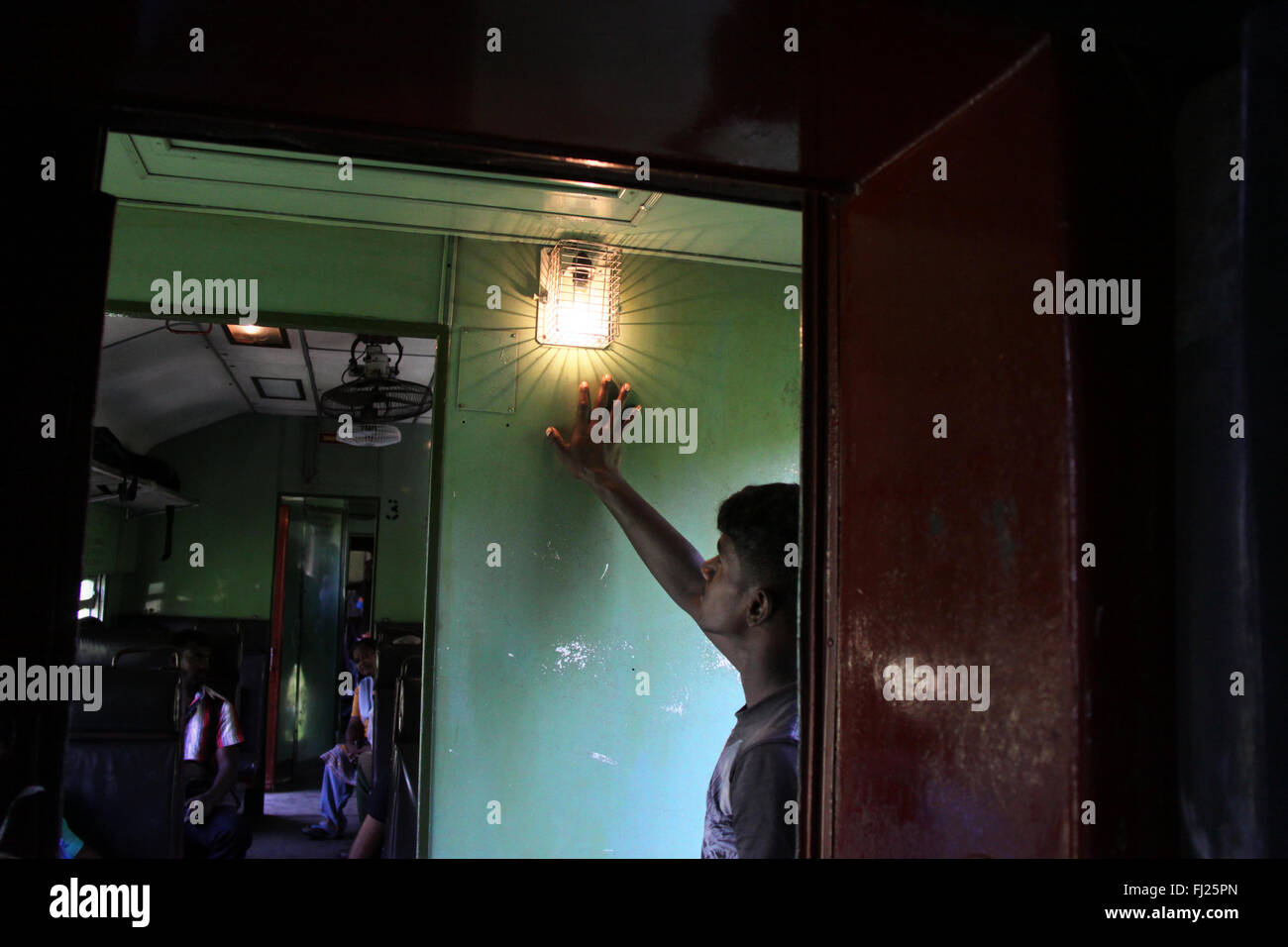 Man looking at light in train in Sri Lanka - Stock Image