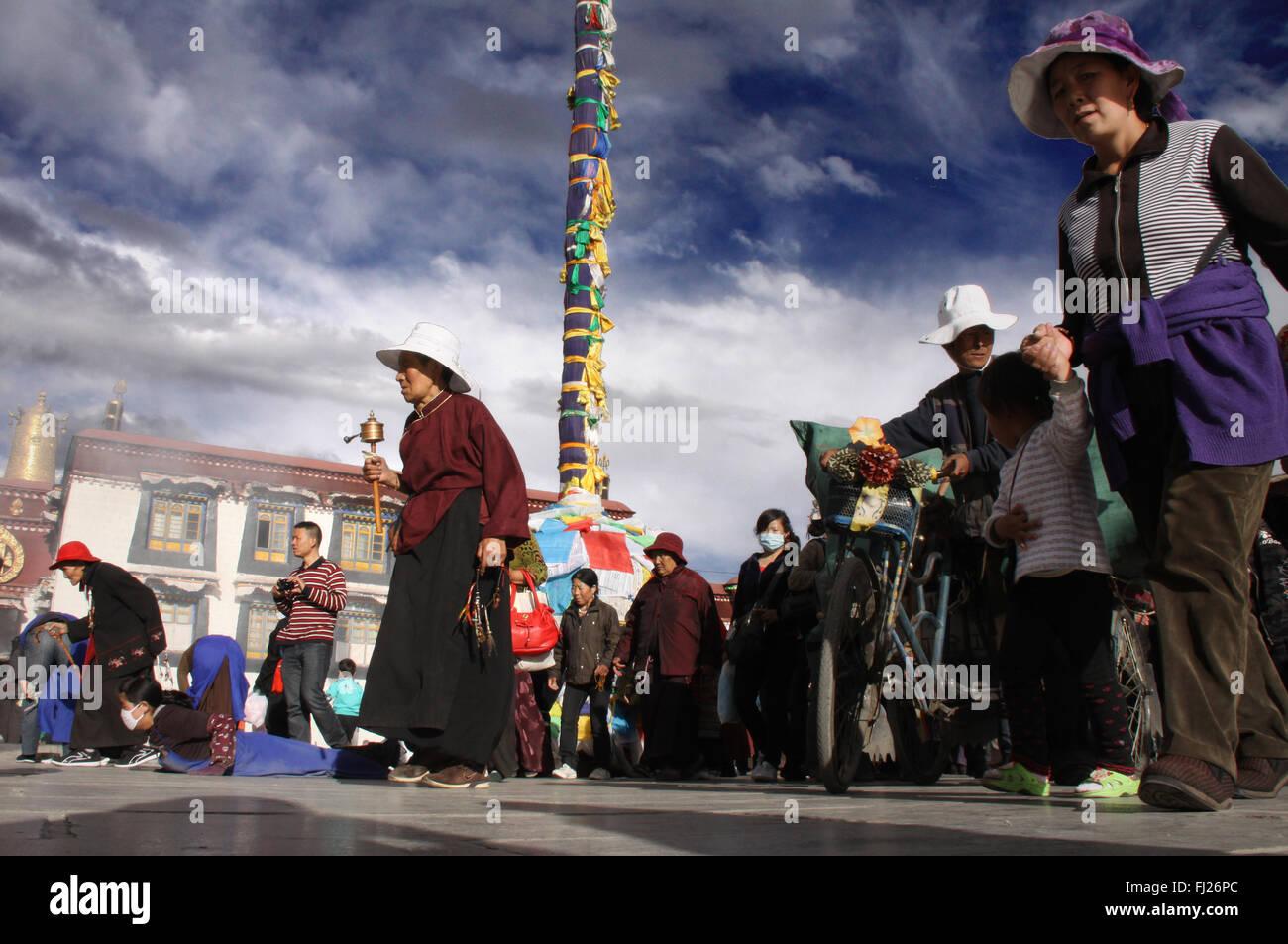 Tibetan people praying / doing Kora around Jokhang temple in Lhasa, Tibet - Stock Image