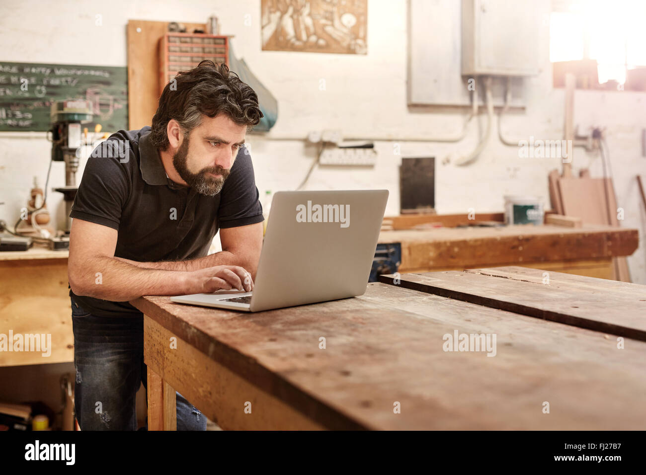 Small business owner in his workshop studio with laptop - Stock Image