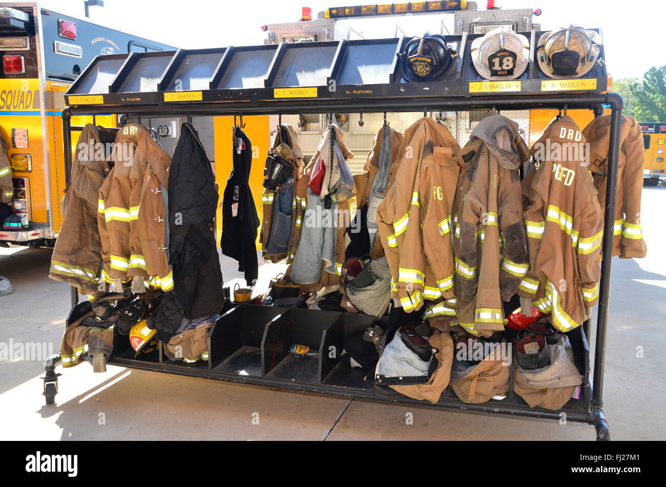 firefighters turnout gear hanging on racks outside - Stock Image