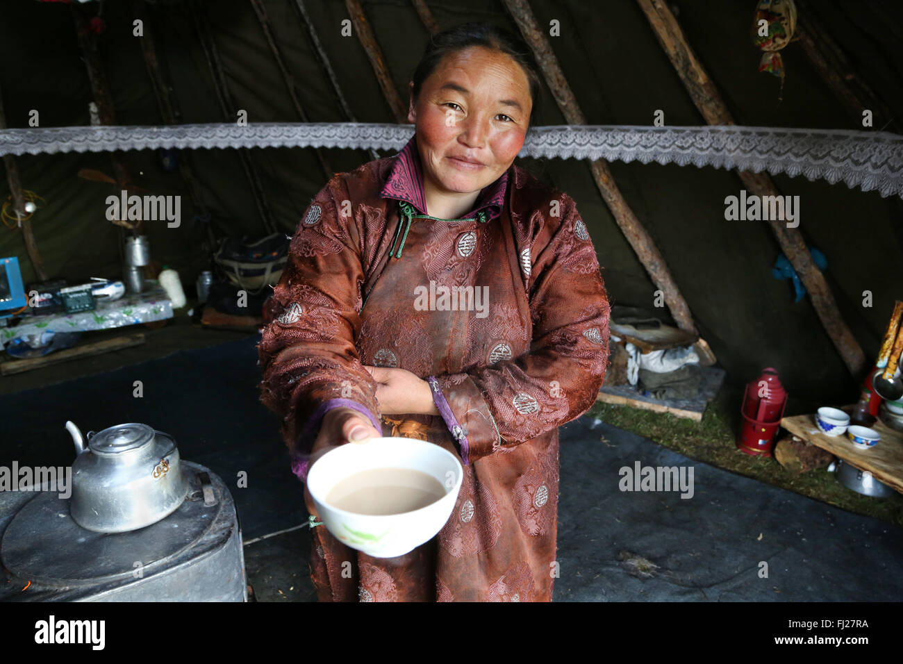 Tsaatan woman offering tea as welcome gift in her ger - Stock Image