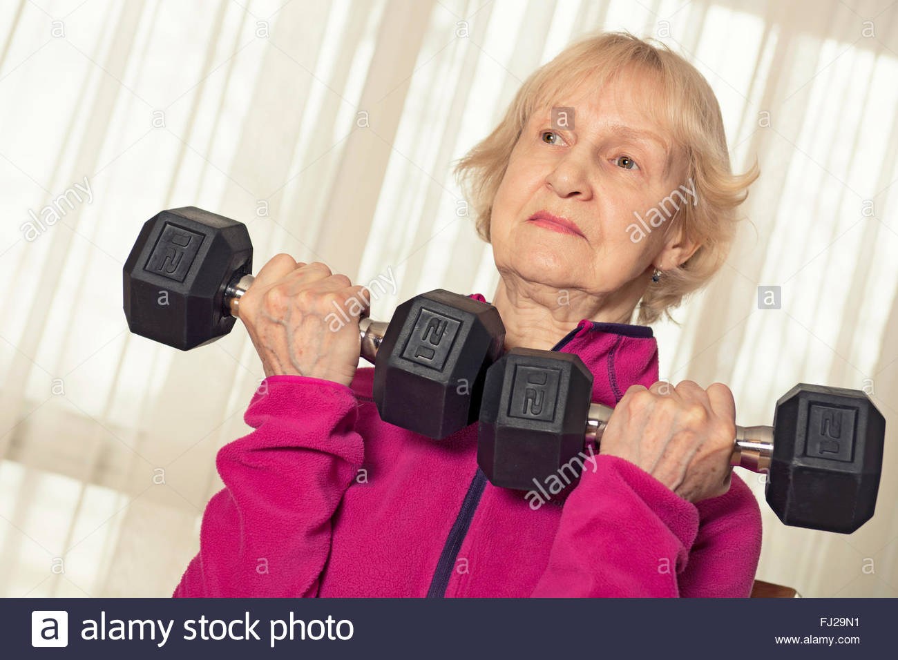 Senior Woman Dumbbells, Elderly Lifting Weights, Weight Training with Dumbbell, 77 year old - Stock Image