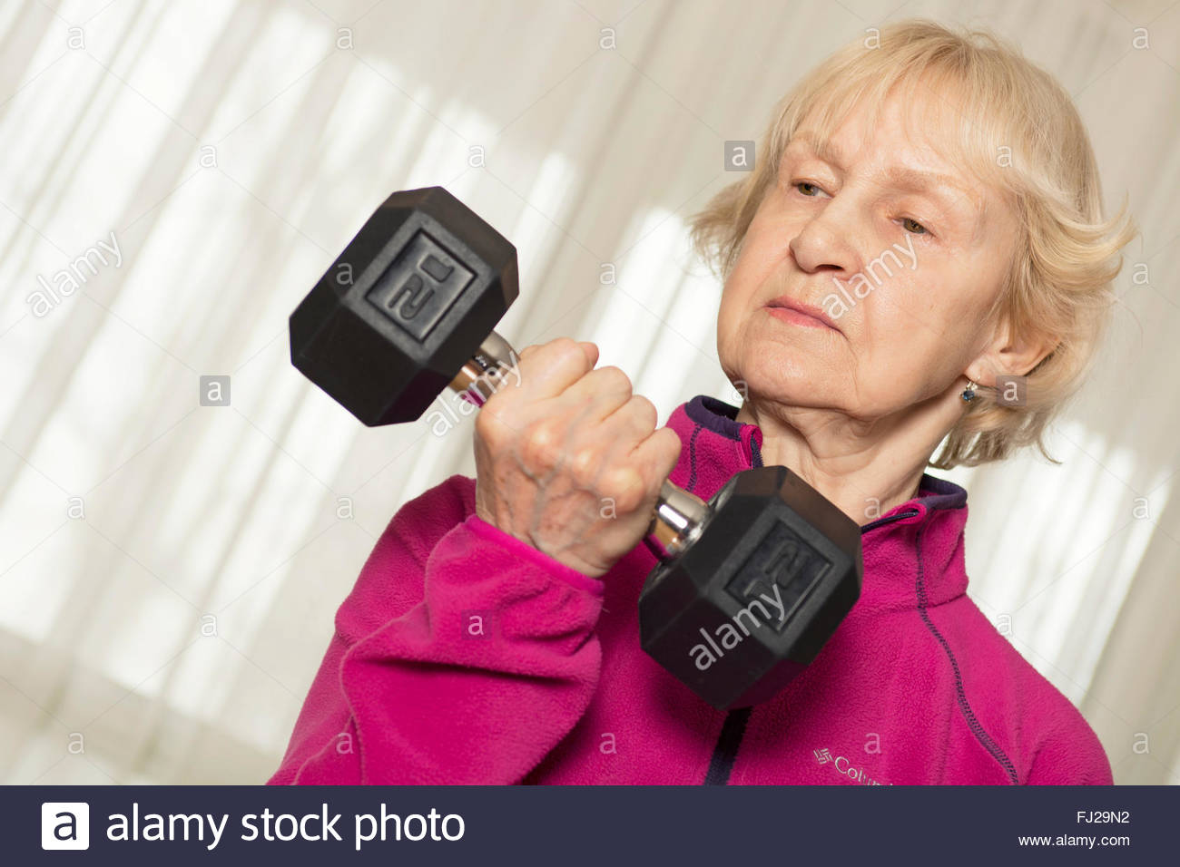 Senior Woman Dumbbell, Elderly Lifting Weights, Weight Training with Dumbbells, 77 year old at home - Stock Image