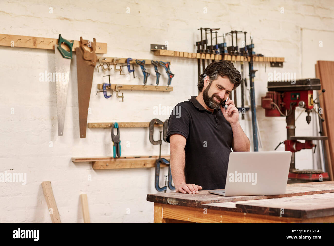 Carpentry small business owner on his phone with a laptop - Stock Image
