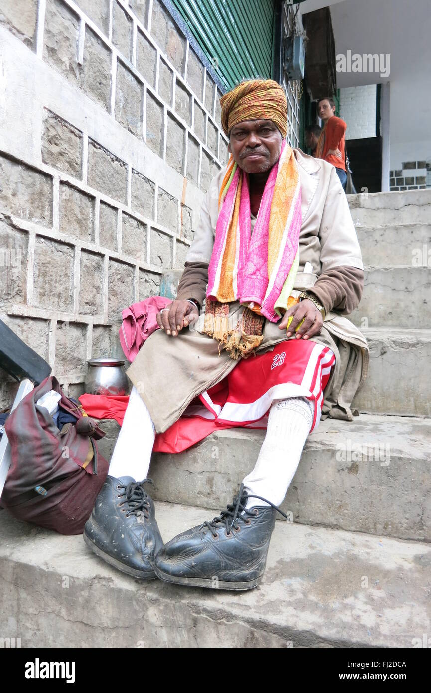 dignified crippled beggar sits on steps in Mcleod Ganj India - Stock Image
