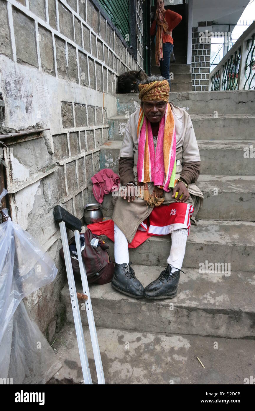Dignified crippled beggar sits on steps with crutch and accepts alms into metal pot in McLeod Ganj India - Stock Image