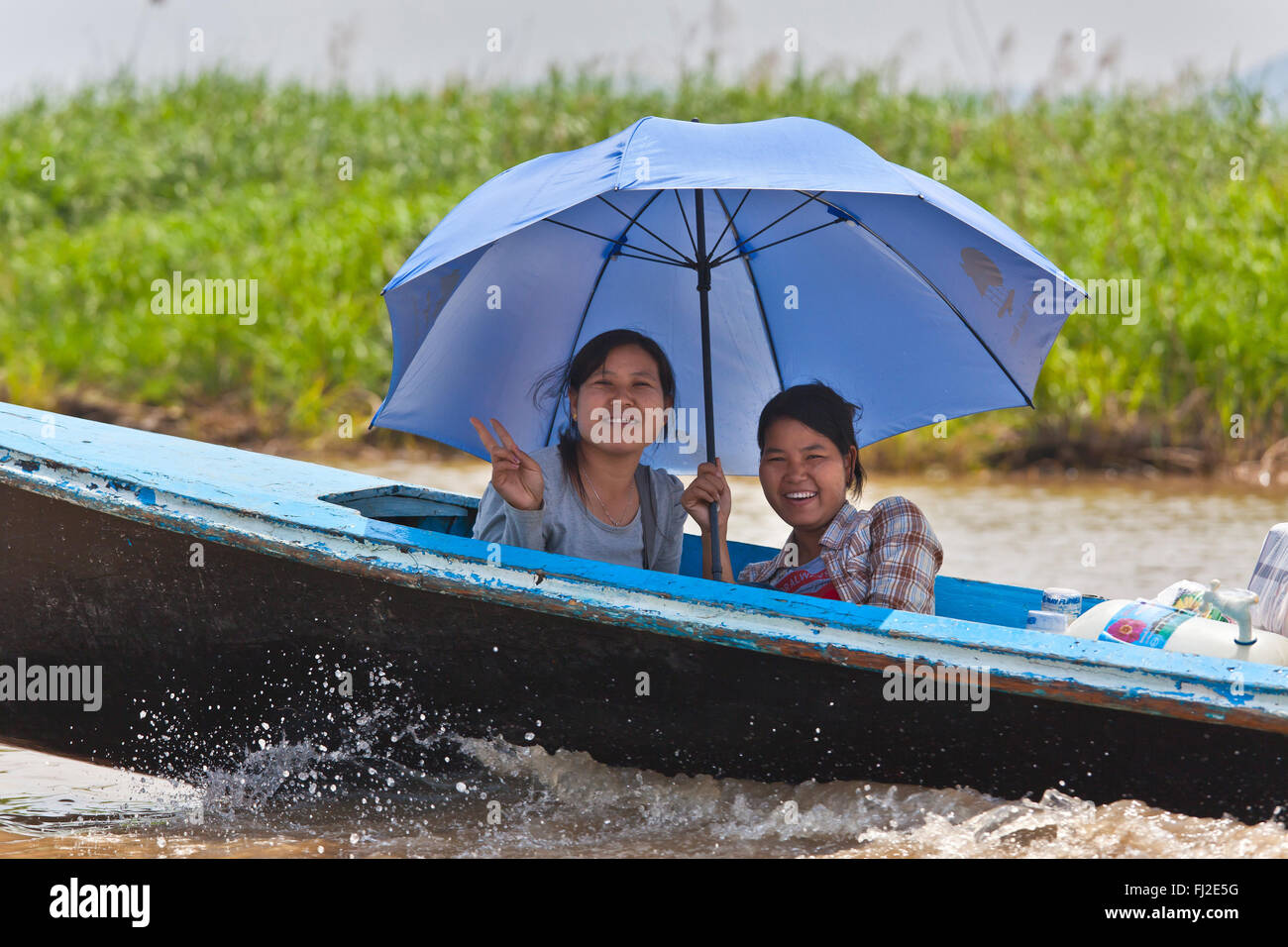 BURMESE woman use an umbrella as sun protection on INLE LAKE - MYANMAR - Stock Image
