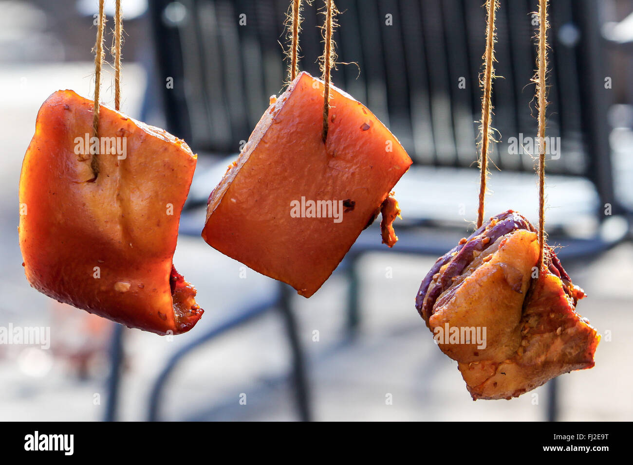 Three bacon hanging outside with backlight - Stock Image