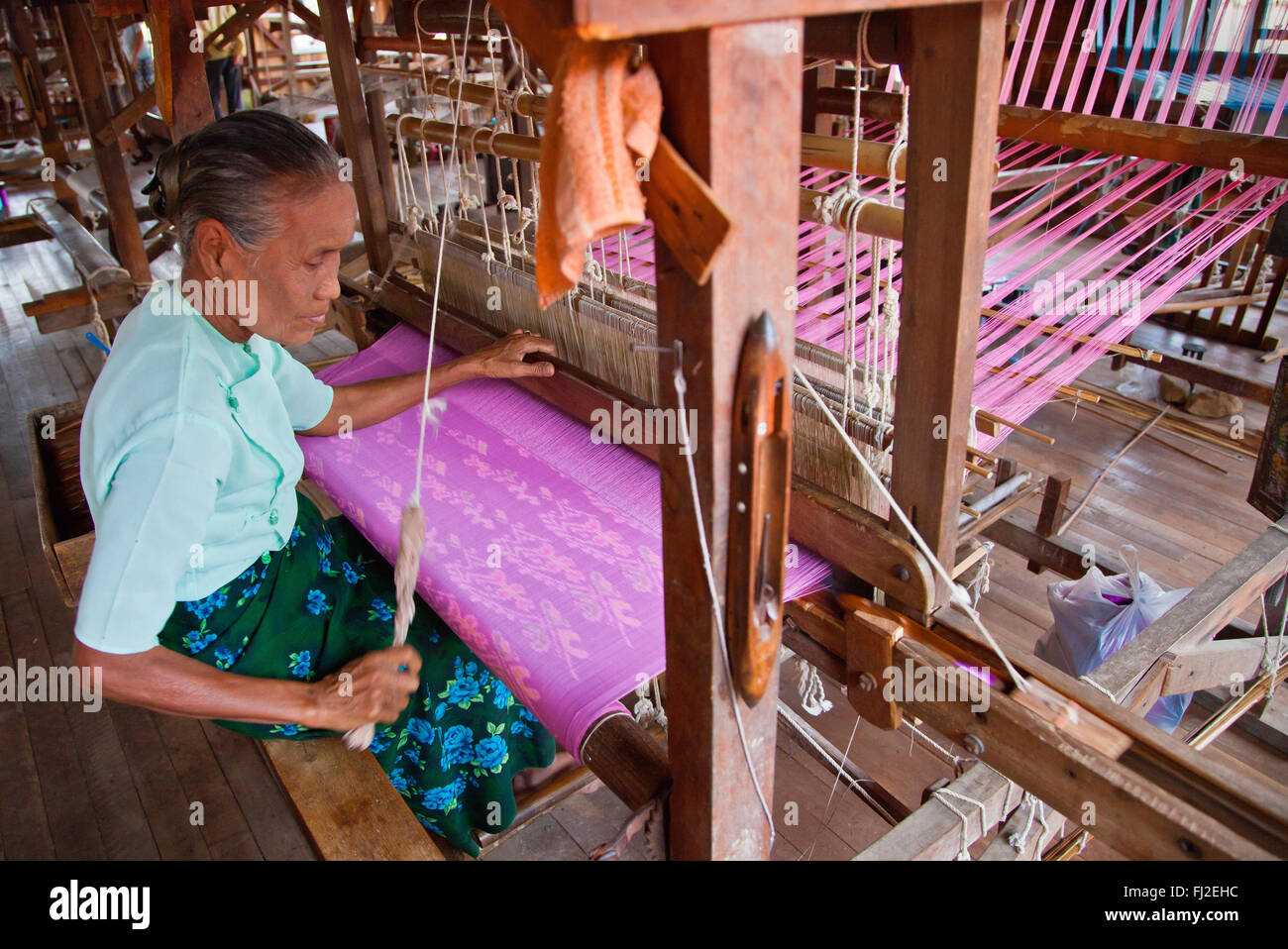 The weaving of LOTUS SILK fabric from the stalks of the lotus plant is a local industry of INLE LAKE - MYANMAR - Stock Image