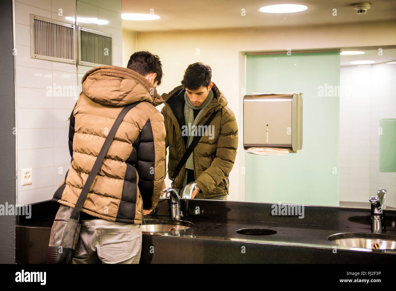 Reflection of young man washing hands in public bathroom - Stock Image