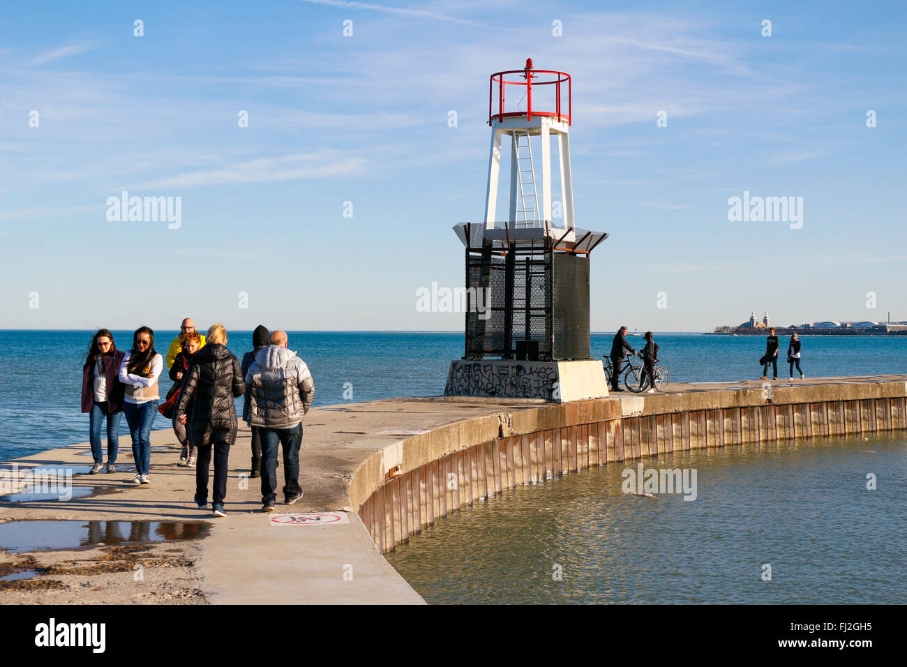 People enjoying a warm February day on the pier at North Avenue Beach. Chicago, Illinois. - Stock Image