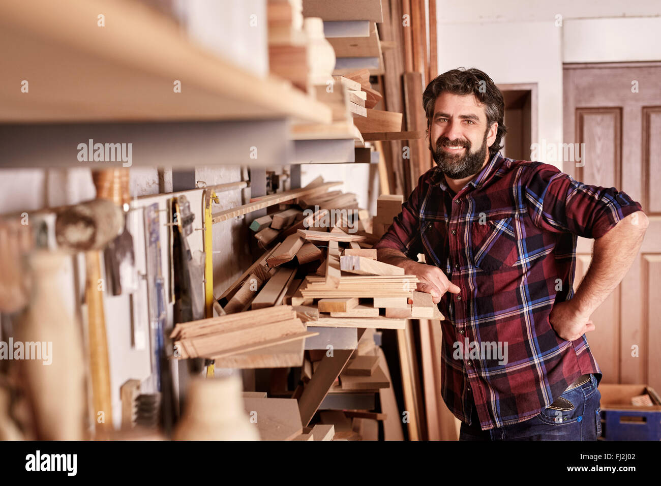 Carpentry business owner standing smiling in his workshop - Stock Image