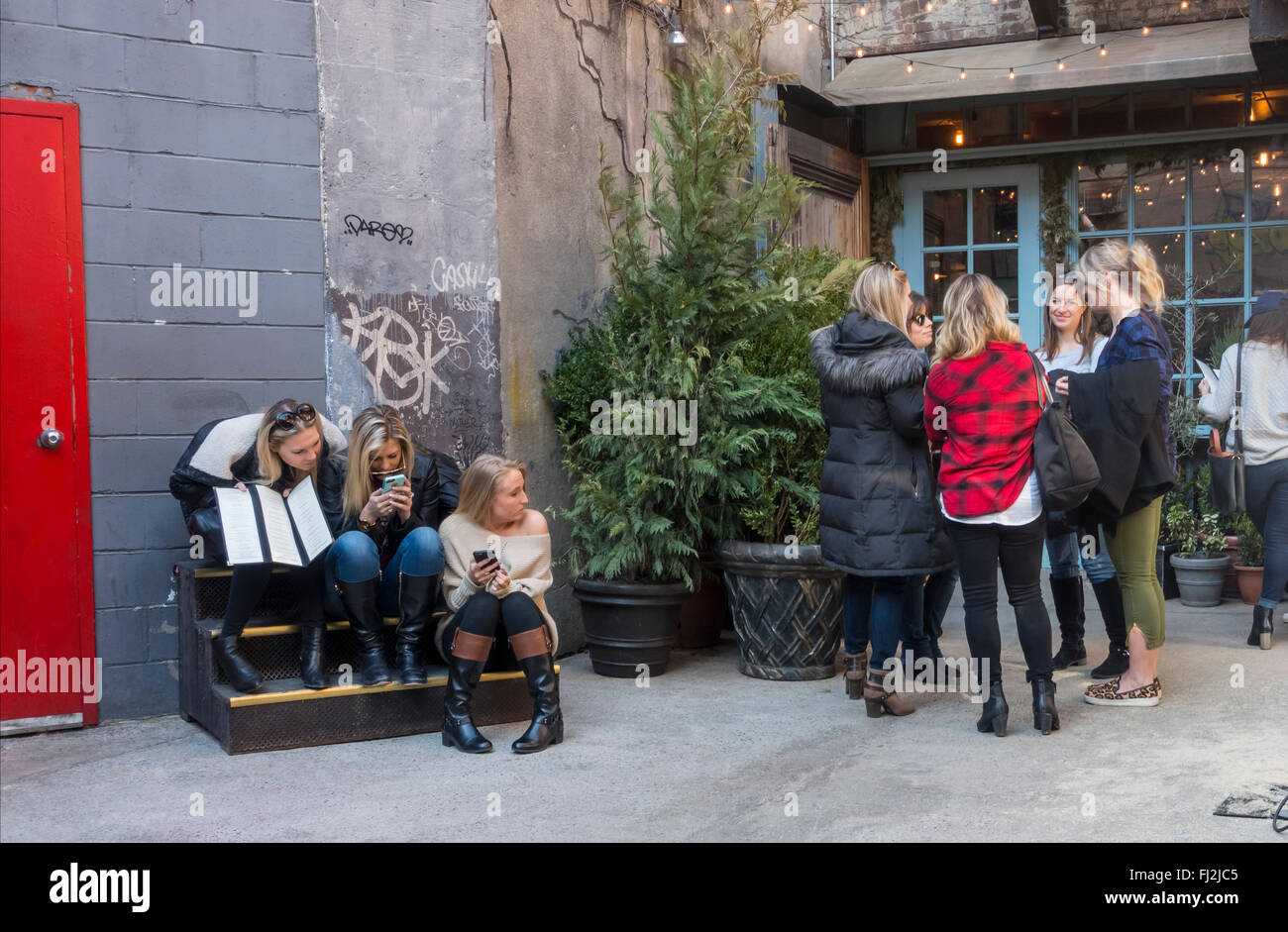 Groups of young women waiting for a table for brunch at Freemans Restaurant in Freemans Alley in New York City - Stock Image