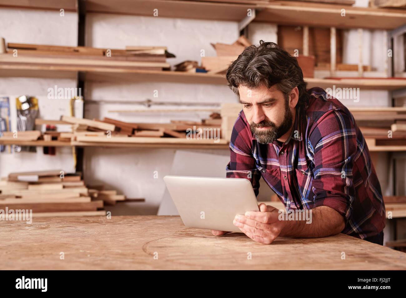Woodwork craftsman in his studio using a digital tablet - Stock Image