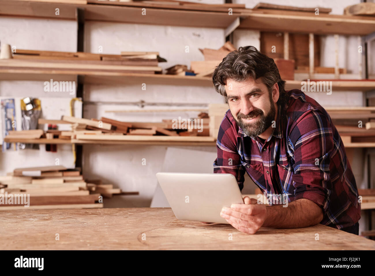 Smiling small business owner in woodwork studio with digital tab - Stock Image