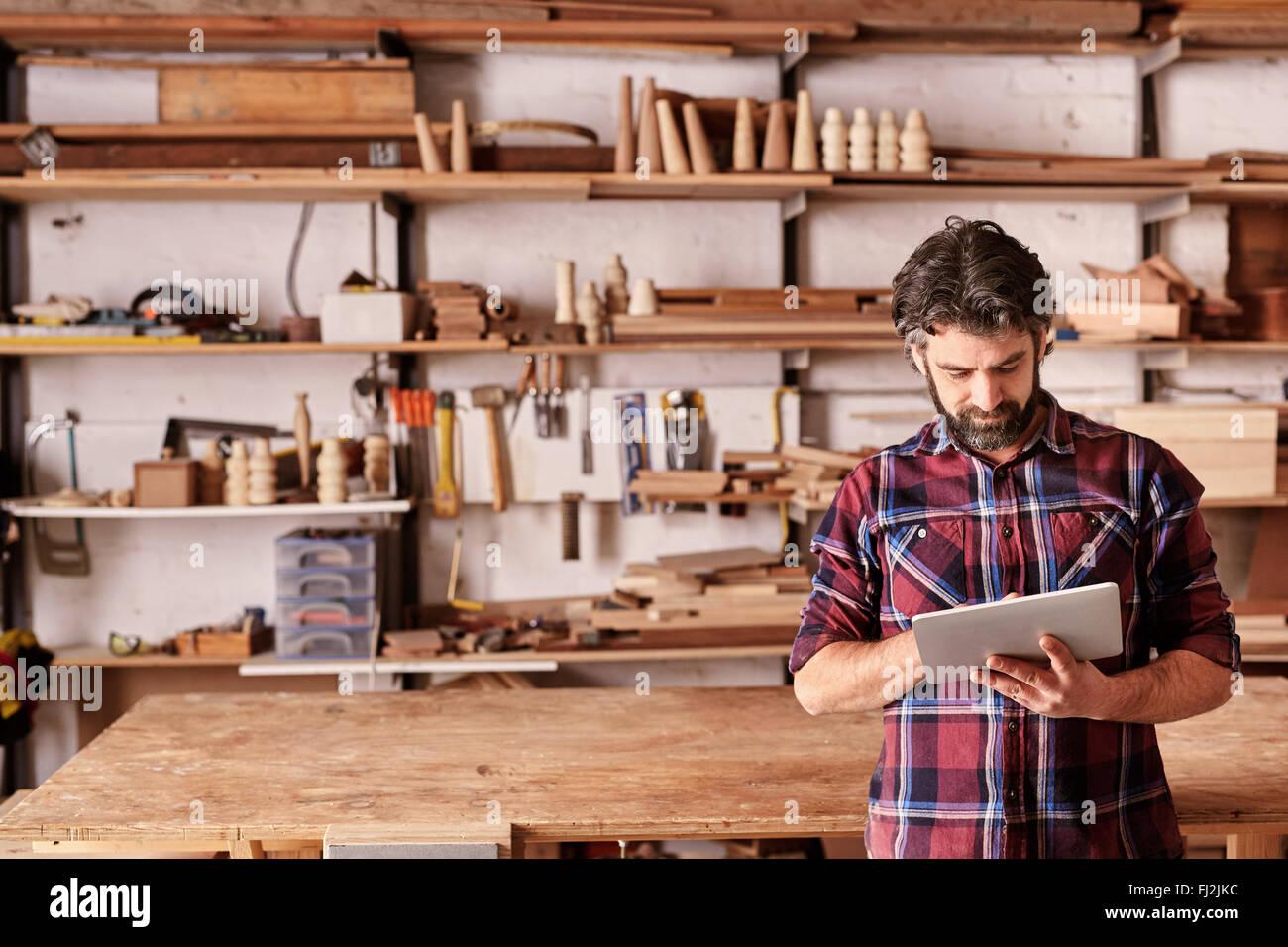 Artisan carpenter in his woodwork studio using digital tablet - Stock Image