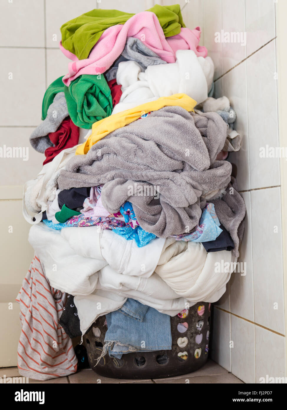 Laundr basket overflowing with dirty clothes and blankets - Stock Image