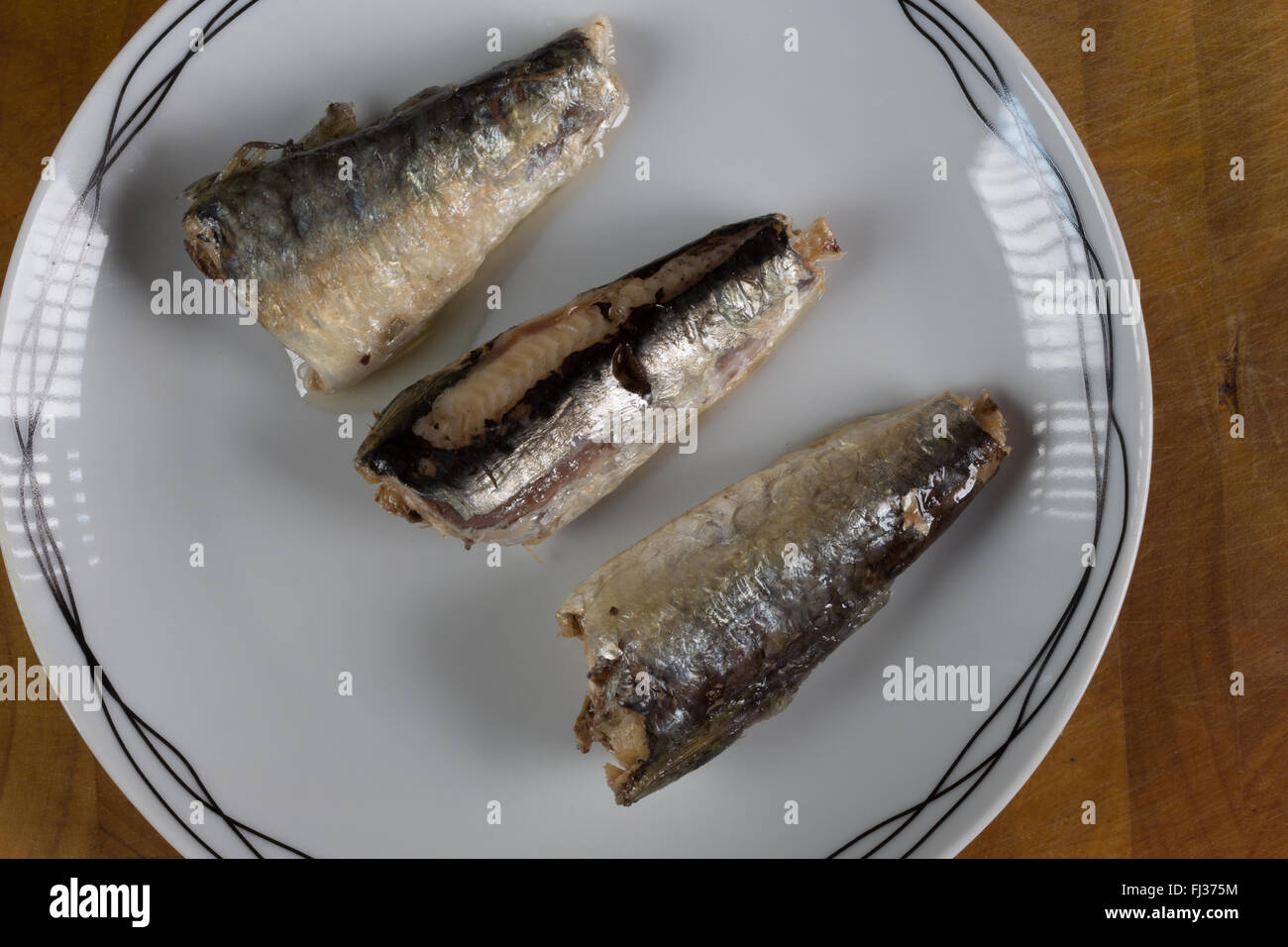 A macro image of canned, ready to eat, Moroccan Sardines in Sunflower oil presented on a white plate. Stock Photo