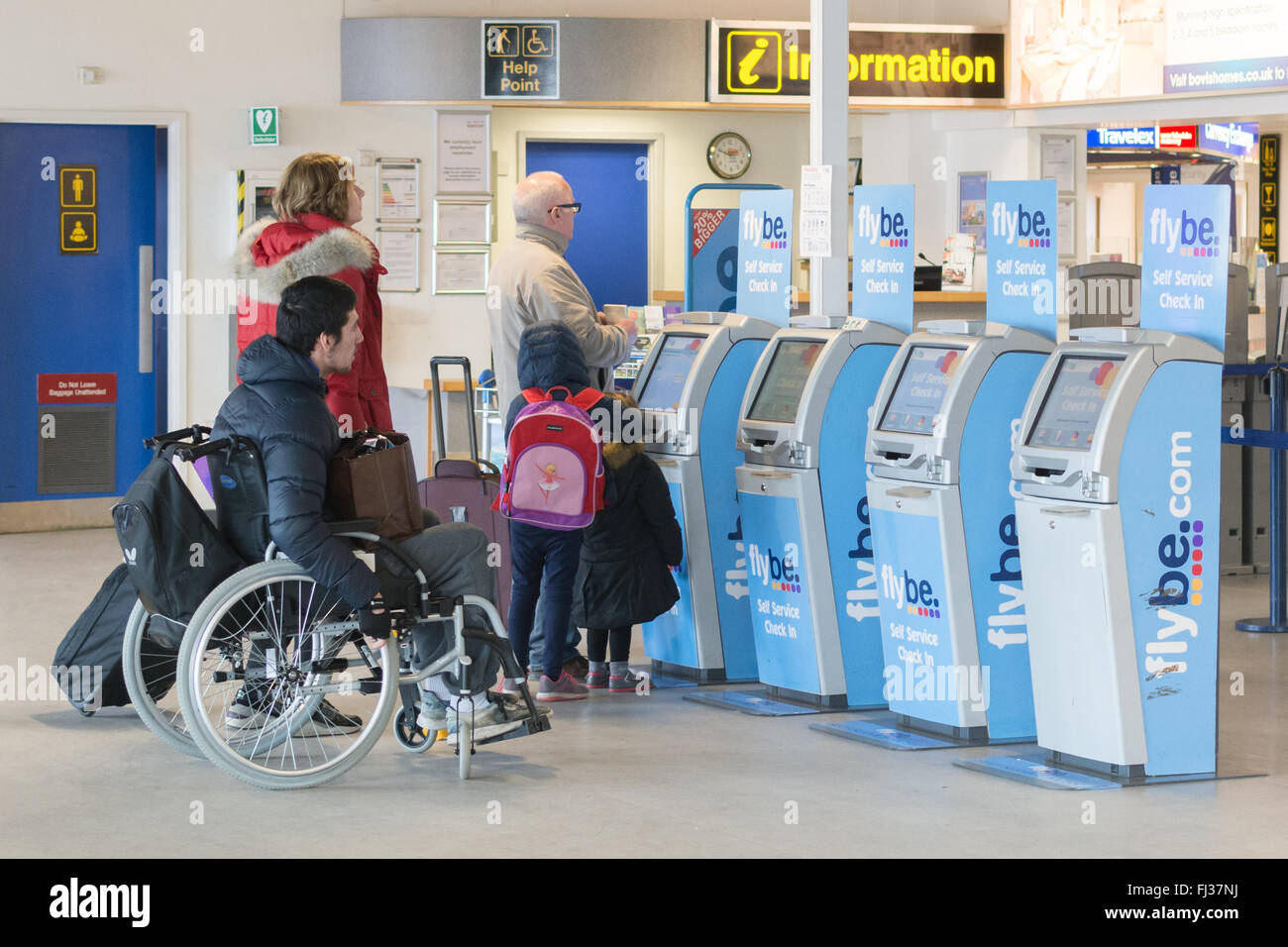 passengers using Flybe self service check-in desks kiosks at Exeter airport, England, UK - Stock Image