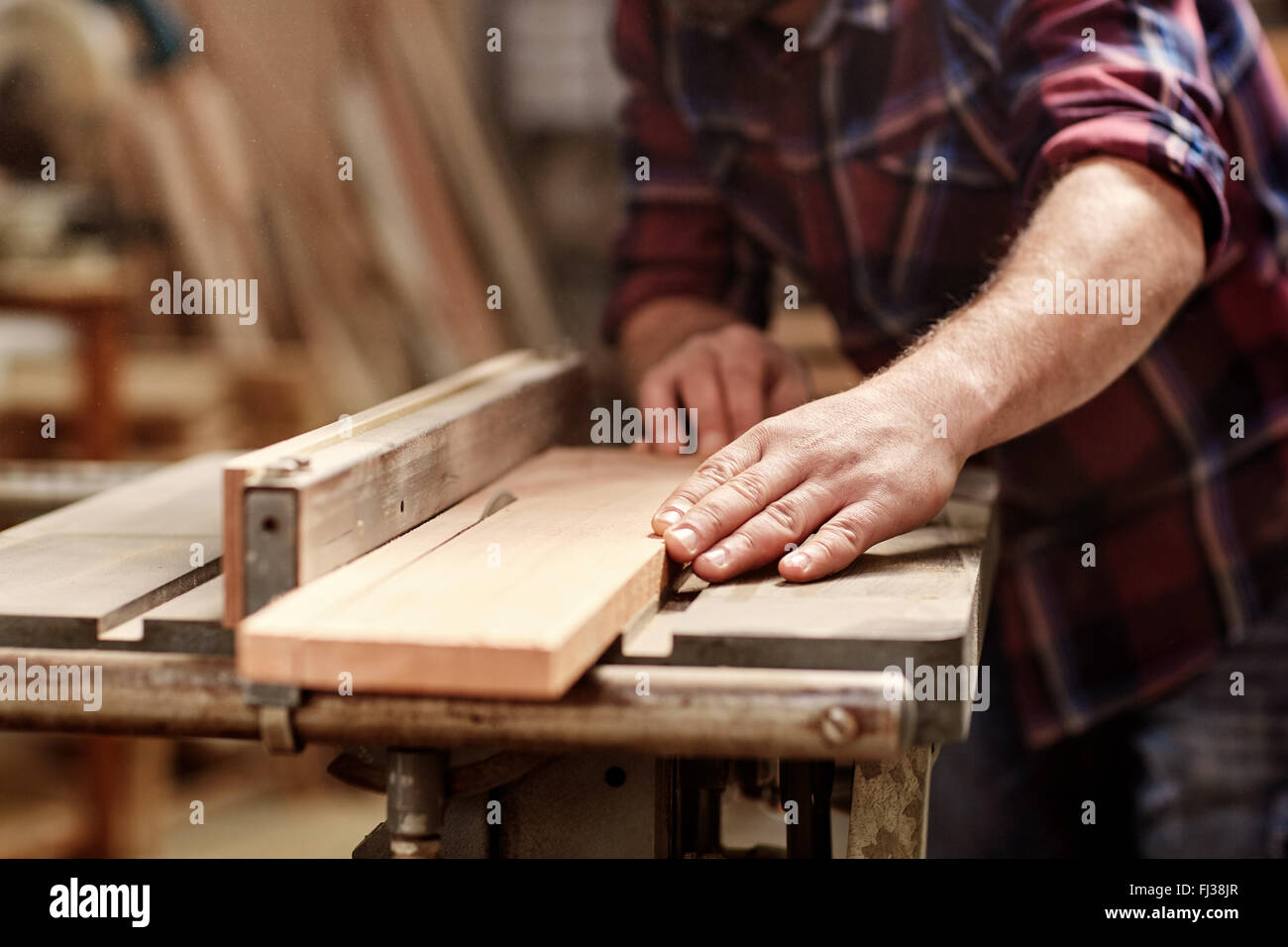 Plank of wood being cut with circular saw in workshop - Stock Image