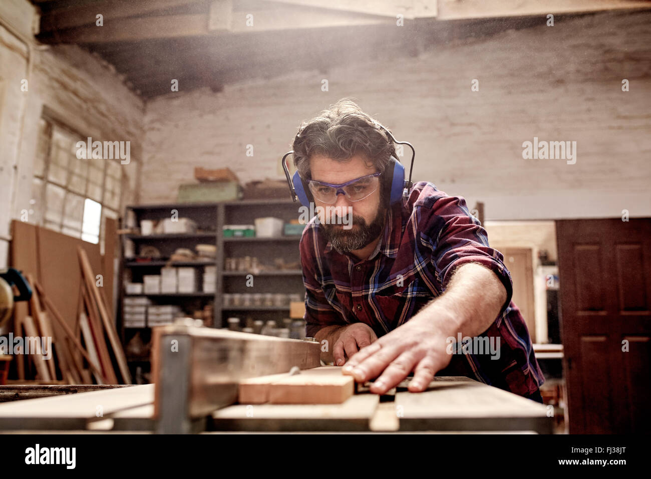 Carpentry business owner cutting a plank of wood in workshop - Stock Image