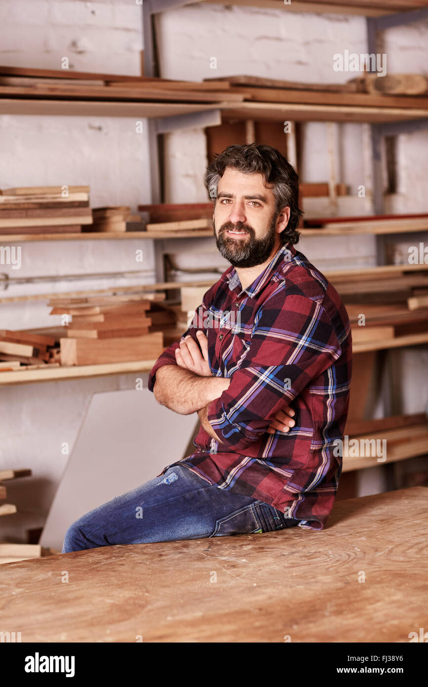 Confident small business owner in a woodwork workshop - Stock Image