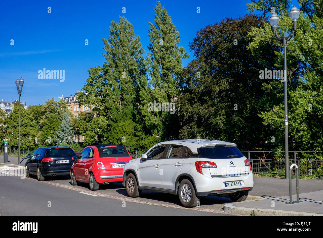 3 cars parked along pavement, Strasbourg, Alsace, France, Europe - Stock Image
