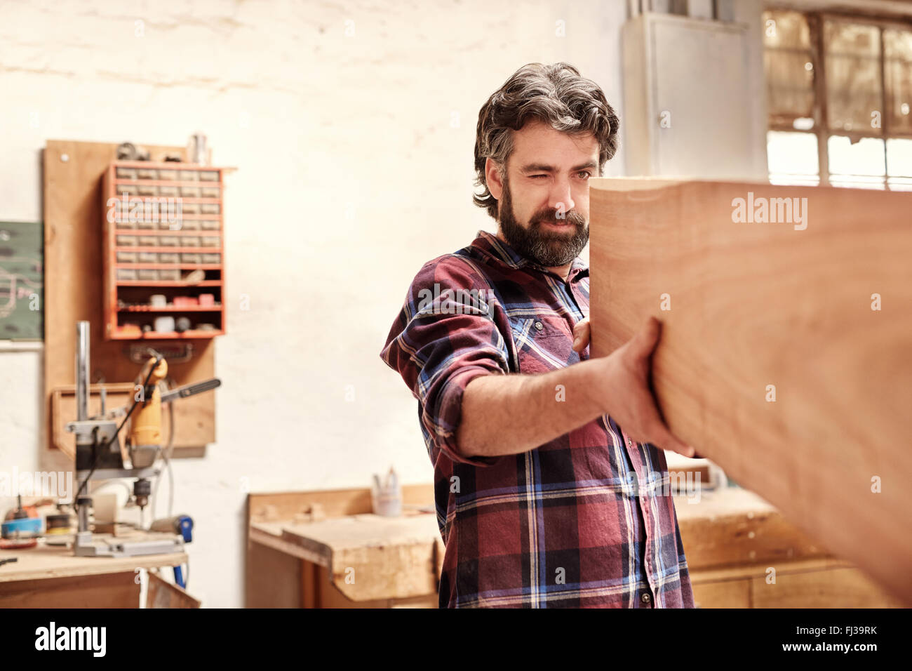 Skilled craftsman inspecting a wooden plank for quality of cut - Stock Image