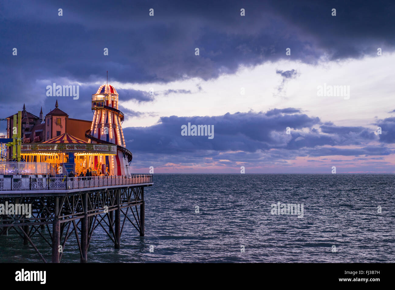 A view from shore of the sea and the amusements on the end of Brighton's Palace Pier taken at dusk - Stock Image