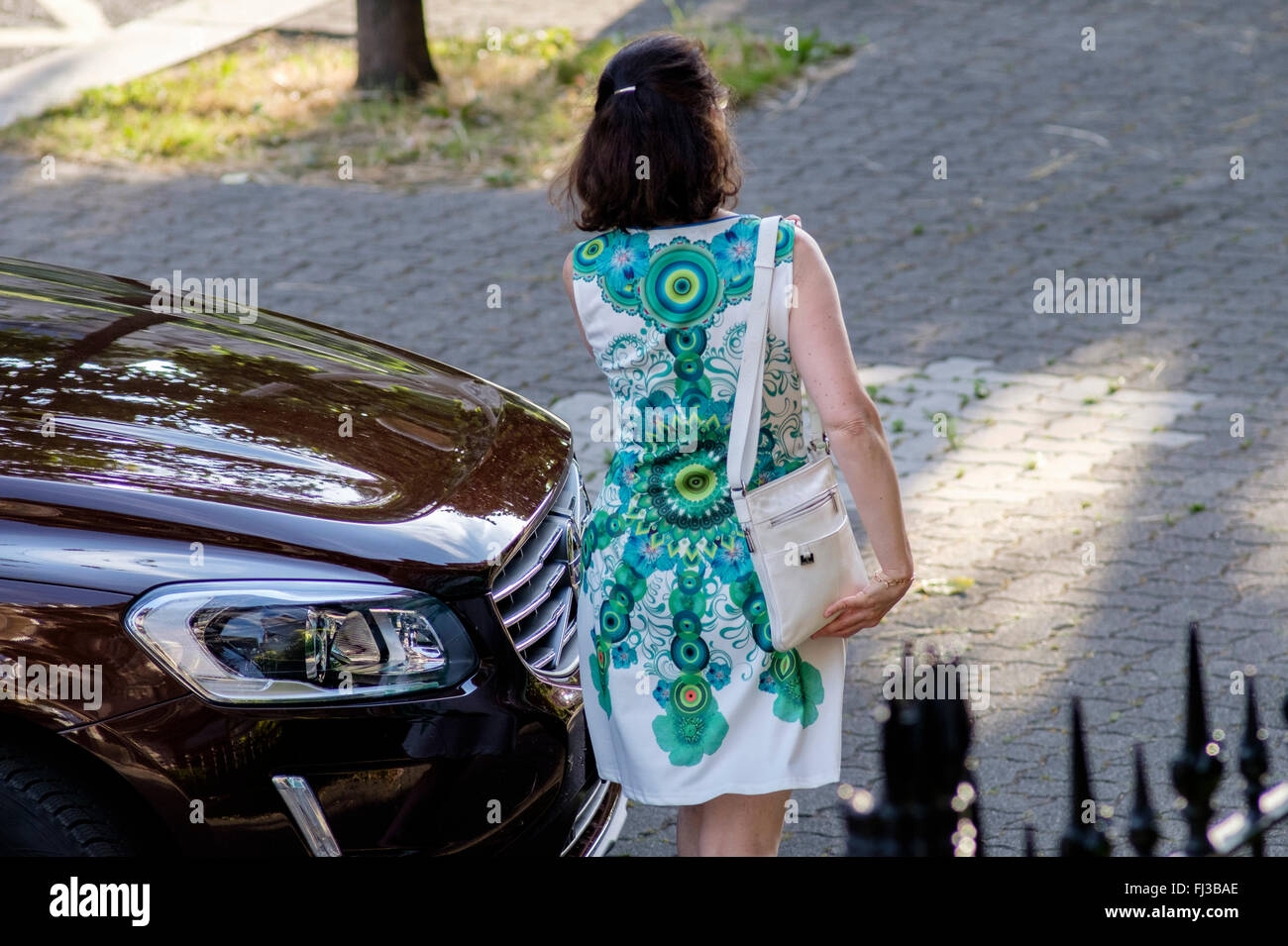 Rear view of woman with green dress walking on street, parked car France Europe - Stock Image