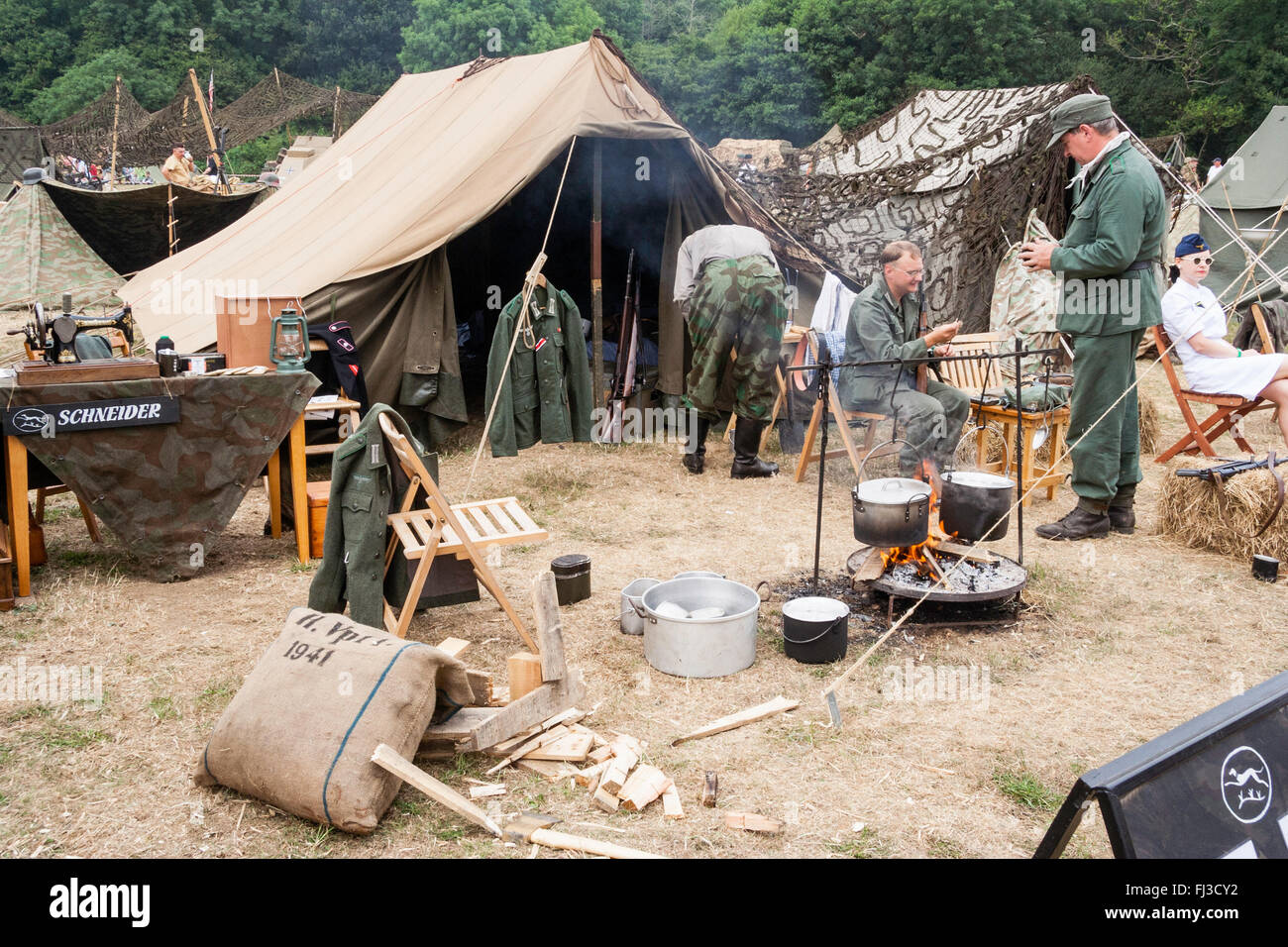 Second world war re-enactment. German encampment with tents, food cooking in pots over fire, soldiers and nurse. - Stock Image