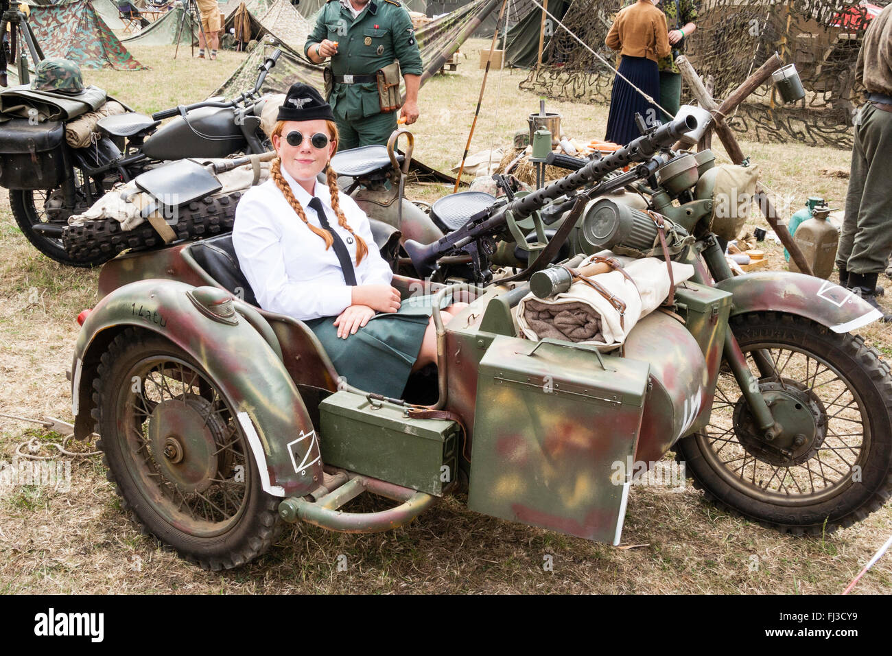 Second world war re-enactment. German motorbike machine gun and side car with young red hairrd uniformed German - Stock Image